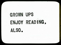 "A black and white slide that says ""grown ups enjoy reading, also"