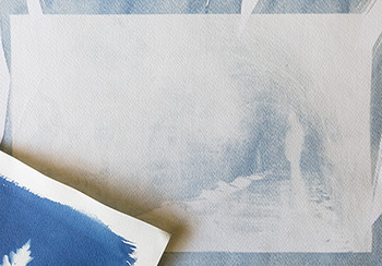two types of cyanotype images on paper - one pale, washed out blue, the other a vibrant cyan blue