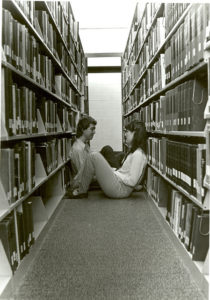two people sit comfortably across from each other between two library shelves full of books
