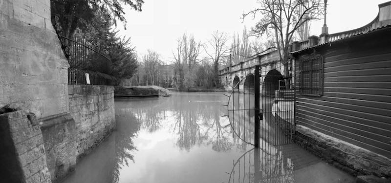 a river, surrounded by stone walls. black and white photo.
