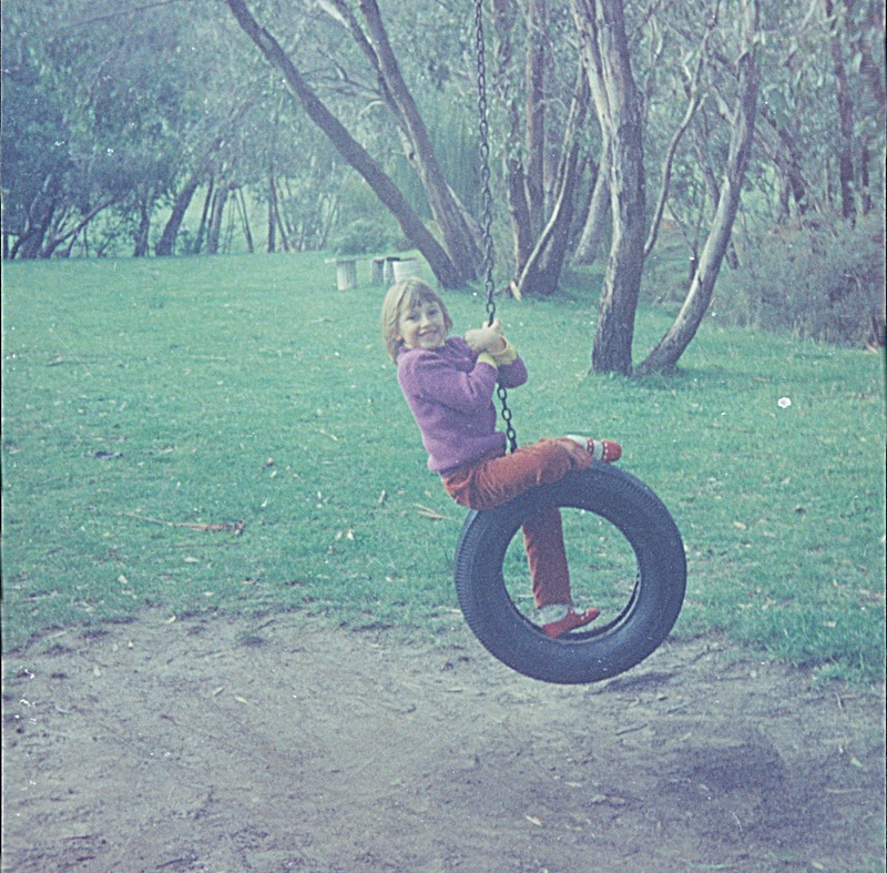 young girl swinging on a tire